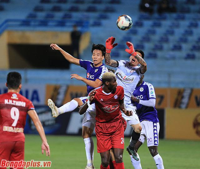 Văn Dũng của Hà Nội FC và thủ môn Thanh Thắng bên phía TP.HCM lao lên tranh bóng bổng