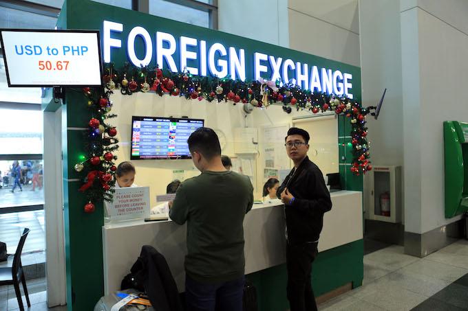 Phóng viên Tú Phạm tranh thủ đổi tiền tại sân bay. Ảnh Đức Cường