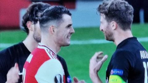 Ảnh chụp màn hình Xhaka tươi cười bắt tay đối thủ trong khi các đồng đội buồn bã vì thua trận