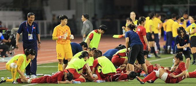 """Các cầu thủ nữ Việt Nam tranh thủ xoa bóp cho nhau để hồi phục về cơ để sẵn sàng bước vào màn """"tra tấn"""" thể lực, tinh thần trong 2 hiệp phụ"""