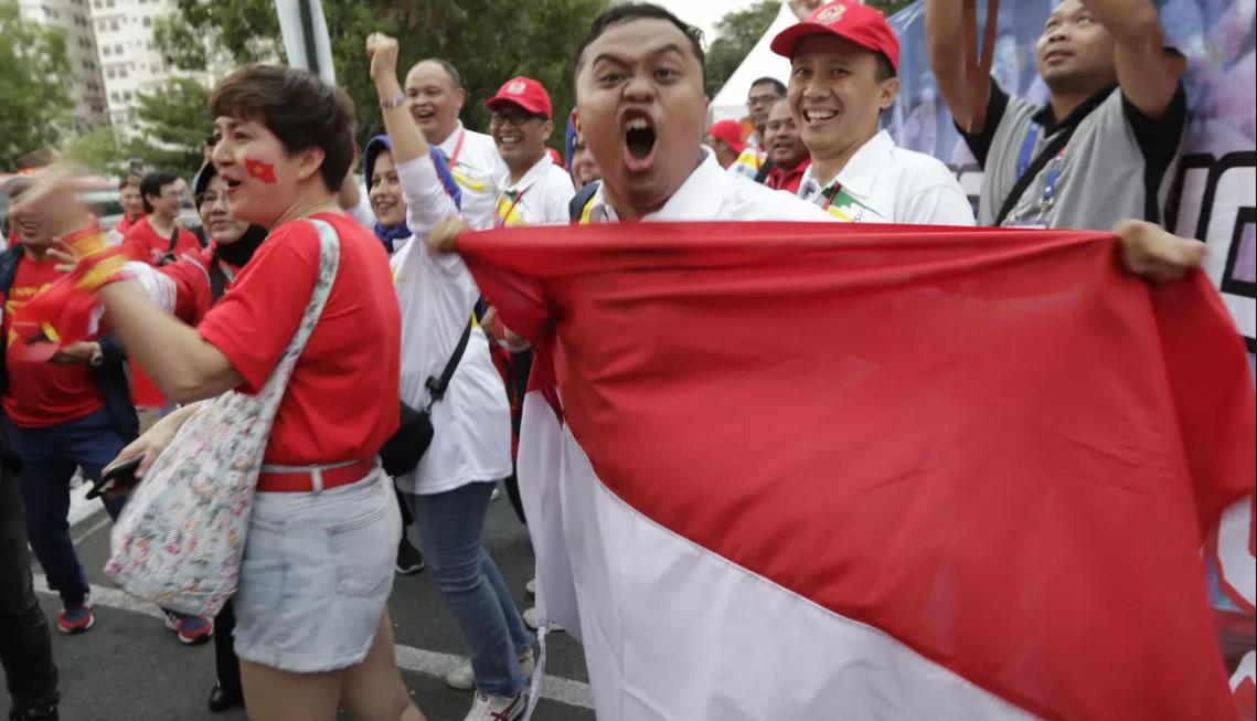 Một CĐV Indonesia đầy hưng phấn bên cạnh 1 CĐV nữ Việt Nam