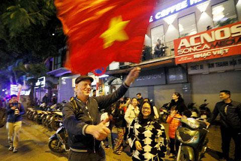 Du khách nước ngoài hòa cùng niềm vui với người hâm mộ Việt Nam cổ vũ chiến tích của thầy trò HLV Park Hang Seo