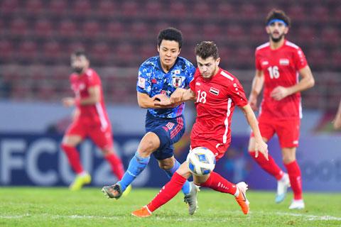 Cầu thủ Nhật Bản (trái) vất vả theo kèm đối thủ Syria