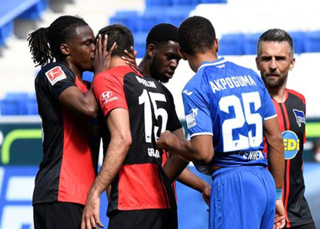 Vui mừng và phấn khích sau khi cầu thủ Kevin Akpoguma của Hoffenheim đá phảnlưới nhà, hậu vệ Dedryck Boyata bên phía Hertha Berlinđã quên mất các quy định khidùng tay ôm lấy khuôn mặt Marko Grujic và hôn má người đồng đội