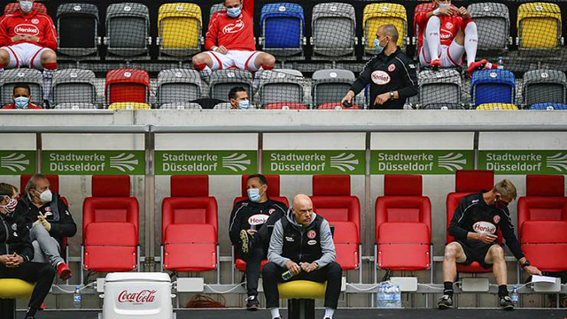 Các cầu thủ Dusseldorf ngồi cách xa nhau ở trên ghế dự bị