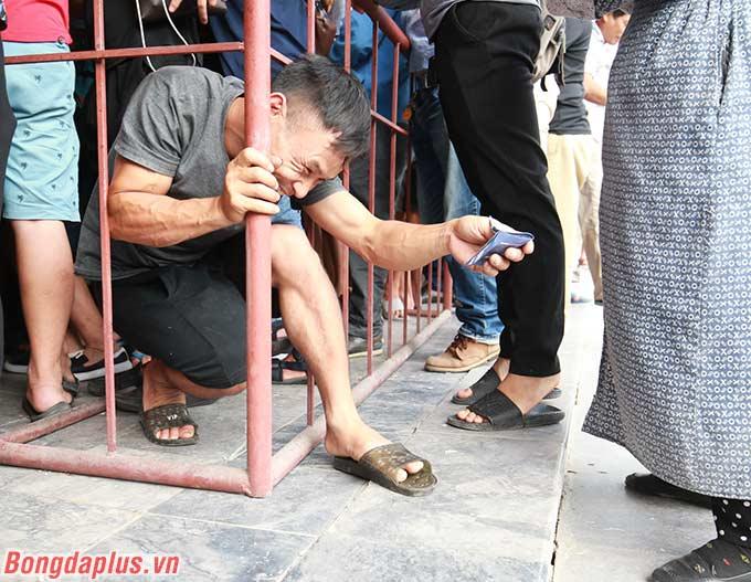 Một CĐV luồn xuống hàng rào để thoát khỏi đám đông. Anh cười tươi vì đã mua được vé