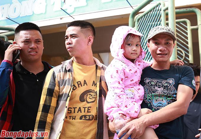 Một CĐV bồng con nhỏ và cùng bạn bè xếp hàng đợi đến lượt. Với họ, đây thực sự là ngày hội bởi suốt thời gian qua bóng đá Việt Nam không thể đón khán giả vì dịch Covid-19