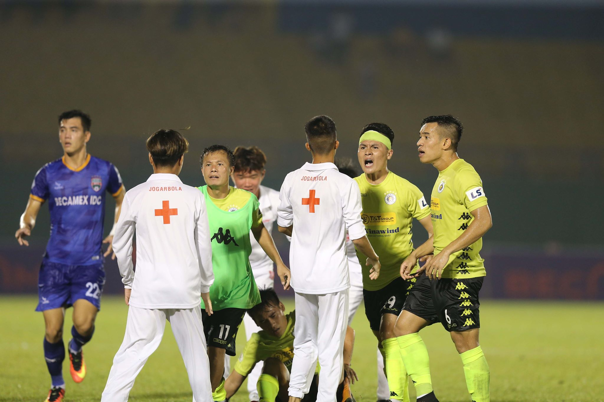 Thành Lương chạy vào sân để chỉ bảo đàn em khiêng cáng trước hành động không đẹp với đồng đội - Ảnh: Quốc An