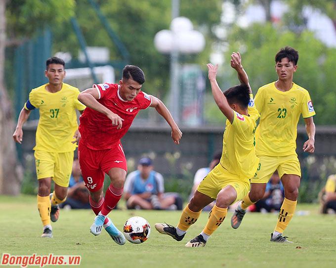 Nguyên Hoàng (đỏ) trong vòng vây của 3 cầu thủ Hà Tĩnh. Tiền đạo này được xem là cầu thủ tiềm năng để phát triển cho bóng đá Việt Nam tương lai nhờ một thể hình lý tưởng