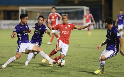 Đội trưởng Sầm Ngọc Đức loay hoay đi bóng trong vòng vây của các cầu thủ Hà Nội FC - Ảnh: Đức Cường