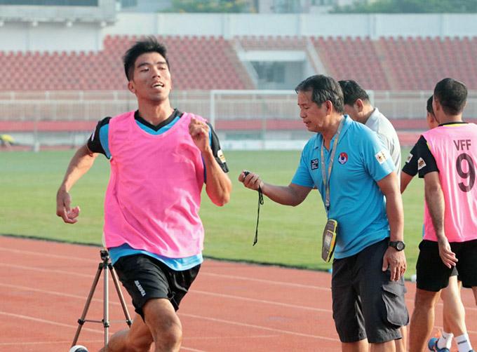 Giám sát Phạm Chu Thiện bấm giờ kiểm tra thể lực - Ảnh: Hữu Thành