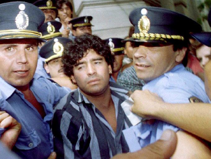 Maradona được cảnh sát hộ tống sau khi rời tòa án vì tội gây thương tích cho một nhà báo ở bên ngoài ngôi nhà của ông tại Mercedes (Argentina) vào năm 1994.