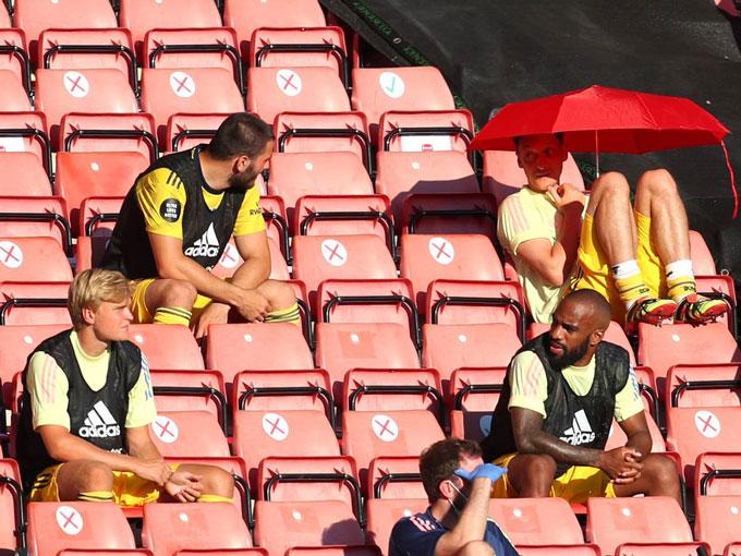Oezil (cầm ô) có mỗi việc ngồi cập nhật Twitter trên khán đài ở các trận đấu của Arsenal