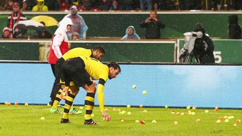 Các cầu thủ Dortmund vất vả dọn cơn mưa banh nỉ từ chính các fan của mình
