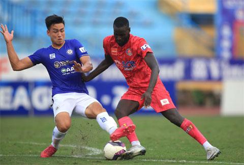 Kebe (phải)  nỗ lực đi bóng trước sự truy cản của  cầu thủ Hà Nội FC   Ảnh: Minh Tuấn