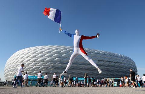 Một CĐV Pháp mặc chiếc áo ba màu và cầm quốc kỳ nhảy lên vui sướng ngoài sân Allianz Arena, nơi diễn ra trận Đức - Pháp