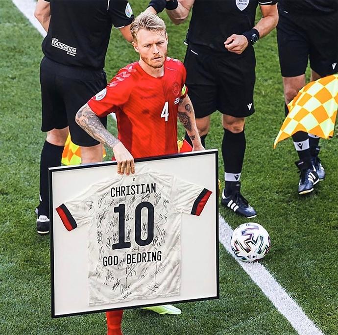 Trước trận đấu, thủ quân Kjaer cùng các đồng đội ở ĐT Đan Mạch đã mang tấm ảnh có in số áo và tên Eriksen có chữ ký của các đồng đội